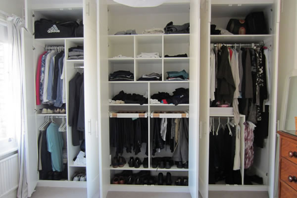 Fitted wardrobe with doors open to show hanging and shelving space